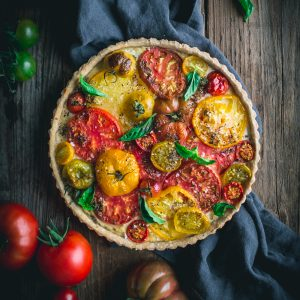 The best and easiest heirloom tomato tart recipe, with ricotta, balsamic caramelized onions, fresh basil, and a buttery tart crust.